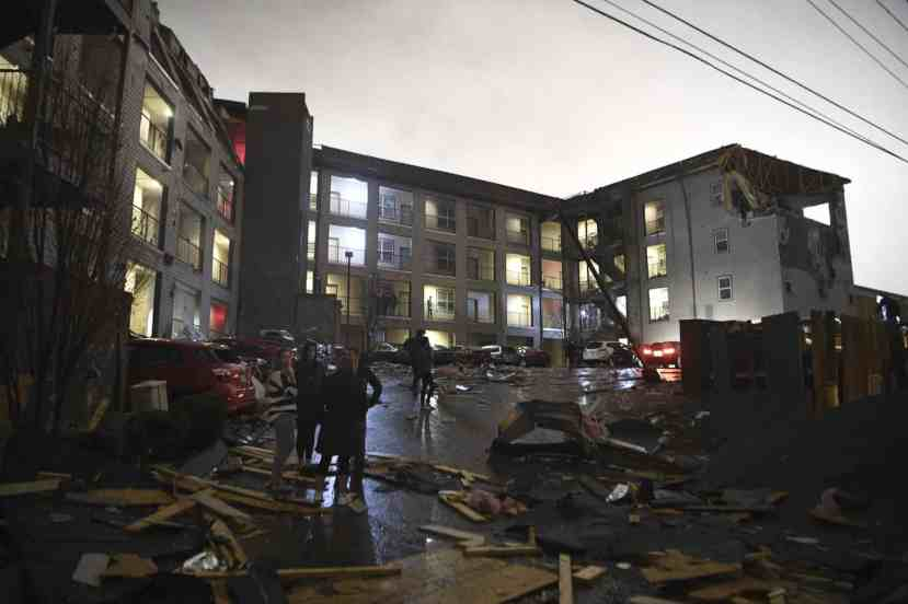 As the sky lightens, debris is scattered across the parking lot of a damaged apartment building Photograph: Courtney Pedroza/AP