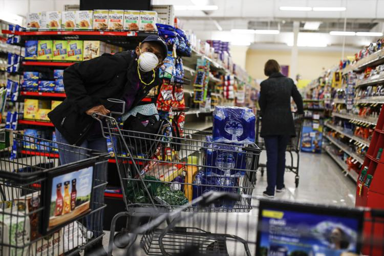 A customer browses aisles Friday, March 20, 2020, while wearing a protective face mask at a Stop & Shop supermarket in Teaneck, N.J.