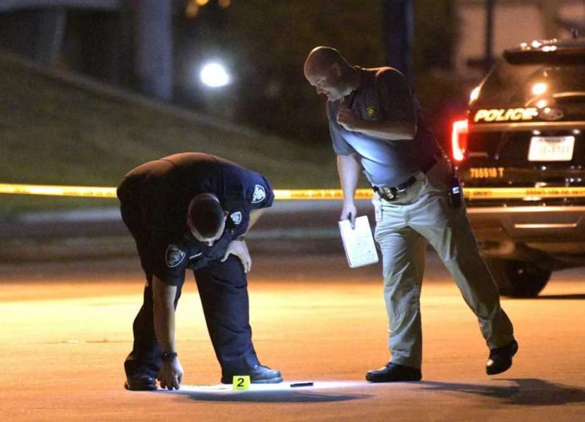 Police look at a machete while they investigate the scene where an officer shot a man