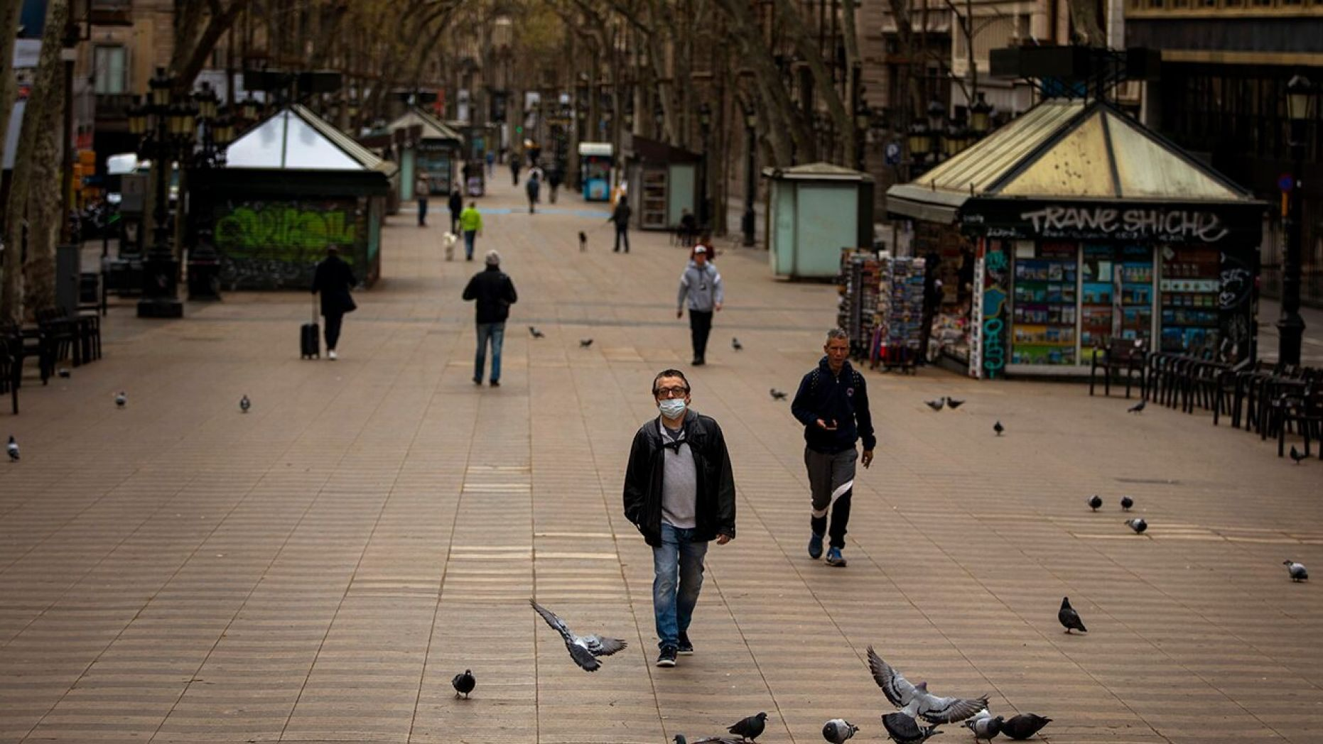 People walk along La Ramblas in Barcelona, Spain, Sunday, March 15, 2020.