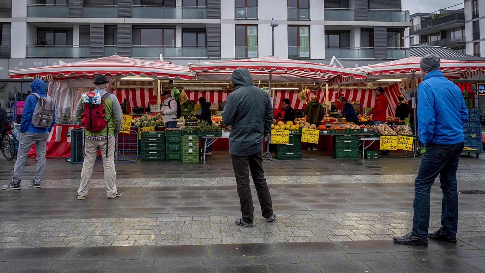People keep distance as they queue on a small weekly market in Frankfurt, Germany