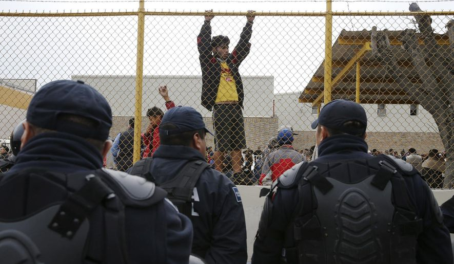 Central American immigrants hang around by the fence line of a shelter guarded by Mexican Federal police in riot gear in Piedras Negras, Mexico, Tuesday, Feb. 5, 2019.
