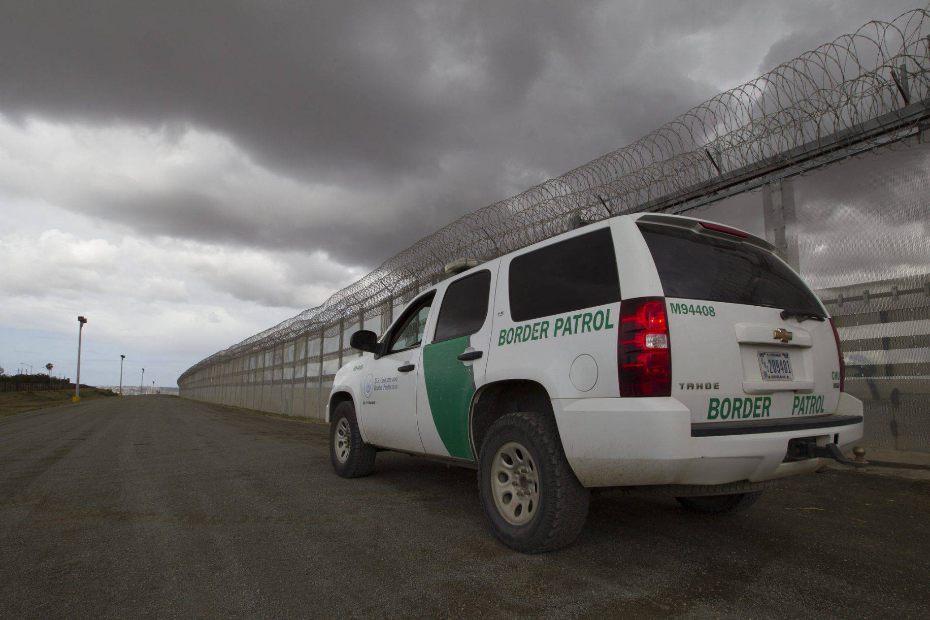A Border Patrol vehicle sits along the border fenceline separating San Diego and Tijuana Mexico watching for illegal crossings in March 2016.