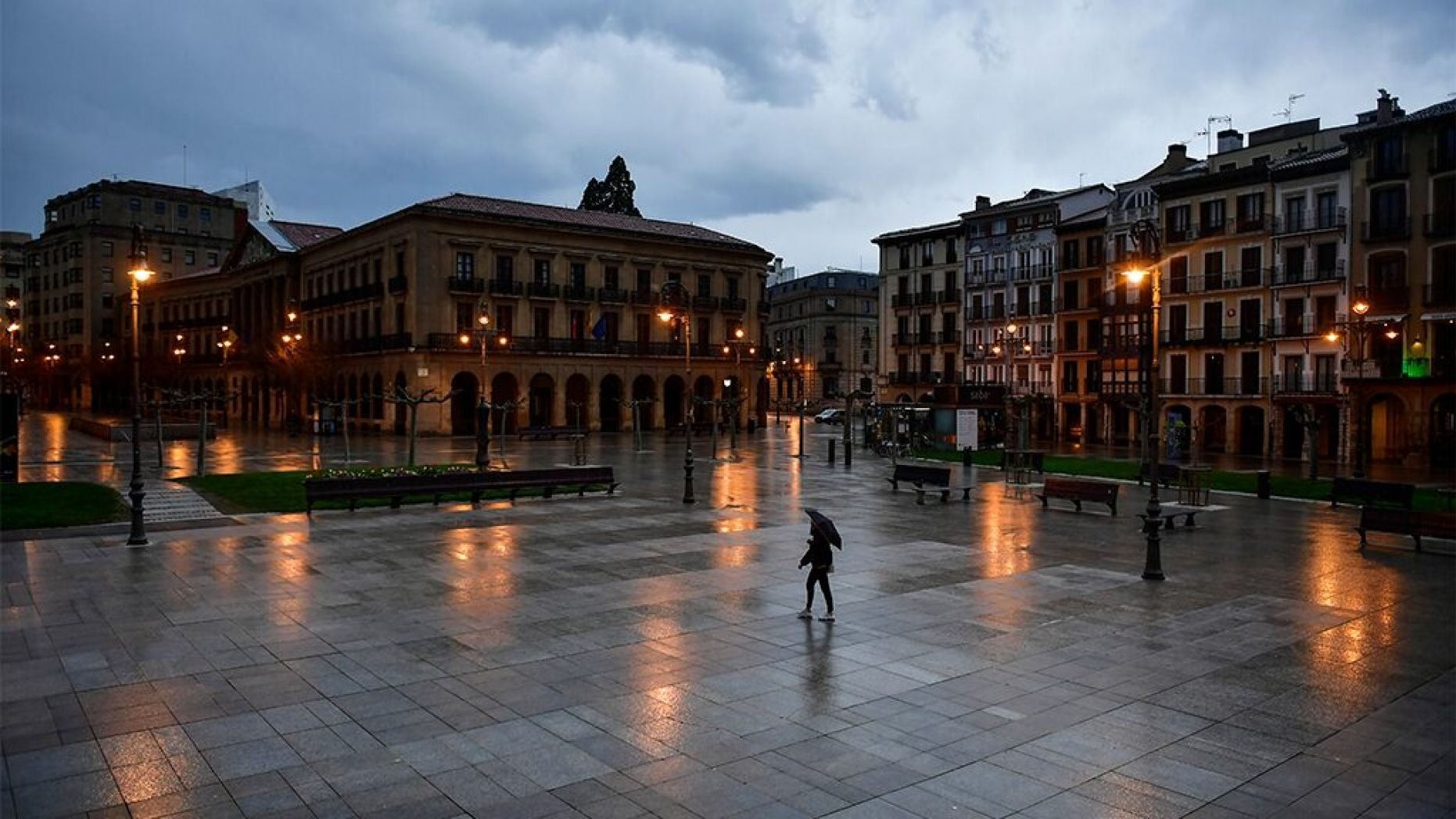 A person walks through an empty Plaza del Castillo square in the old city, in Pamplona, northern Spain, Sunday, March 15, 2020.