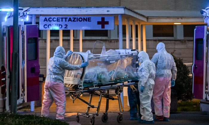 Medical workers in overalls stretch a patient under intensive care into the newly built Columbus Covid