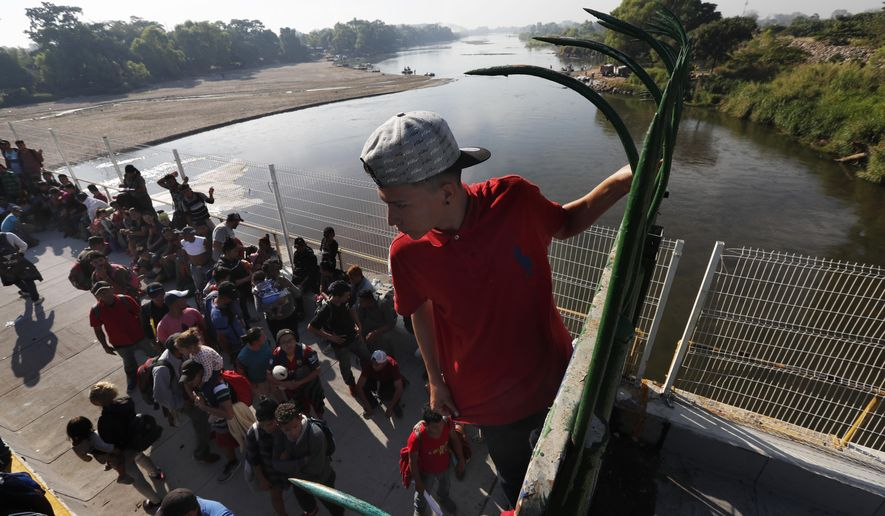 A migrant climbs the fence at the border crossing between Guatemala and Mexico in Tecun Uman, Guatemala, Saturday, Jan. 18, 2020.
