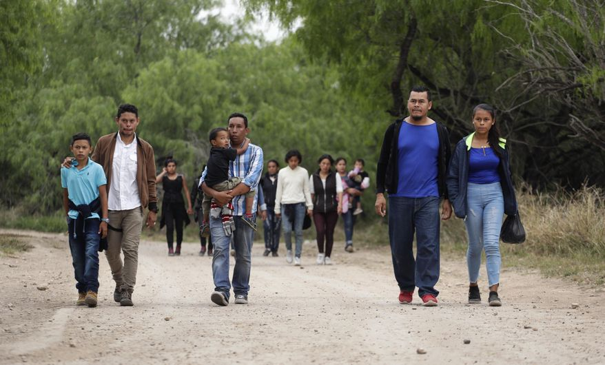 In this Thursday, March 14, 2019, photo, a group of migrant families walk from the Rio Grande, the river separating the U.S. and Mexico in Texas, near McAllen, Texas.