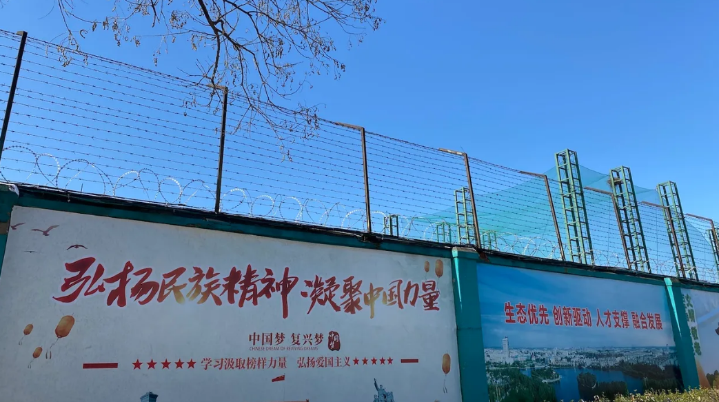 The posters on the wall alongside the Qingdao Taekwang Shoes Co. factory -- the side where the Uighur workers enter and exit, and live in dorms