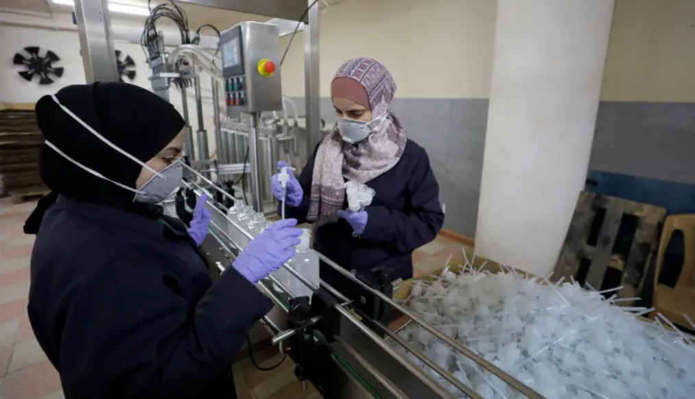 Palestinian women work in a sanitiser factory amid precautions against the coronavirus