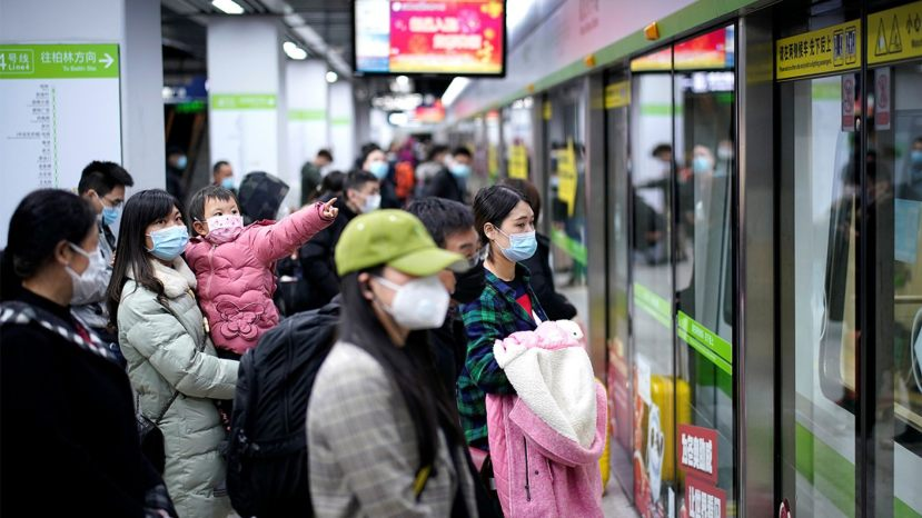 People wearing face masks wait for a subway train on the first day the city's subway services resumed following the novel coronavirus