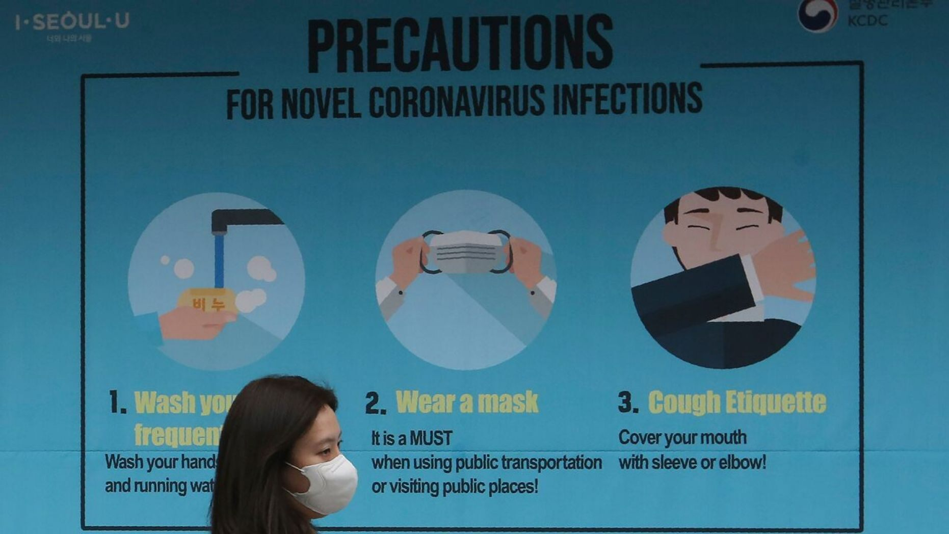 A woman wearing a face mask passes by a poster about precautions against the coronavirus in Seoul, South Korea,