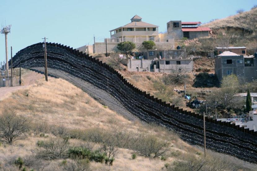 Barbed wire has been placed on top and side of the fence along the United States-Mexico border, shown here, heading East from Nogales, Arizona, in February 2019.