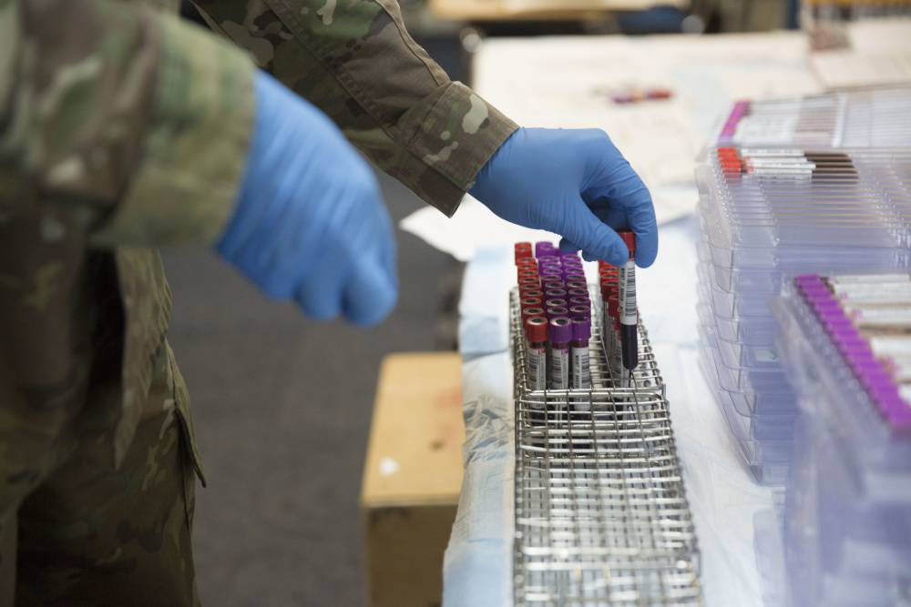 An Army medic sorts through blood samples for prescreening during a Walking Blood Bank training program at Camp Lejeune, N.C.,