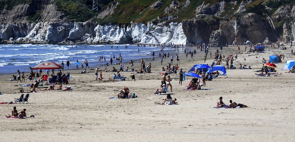In this Saturday, April 25, 2020, file photo, people gather on the beach in Pismo Beach, Calif., on the state's Central Coast.
