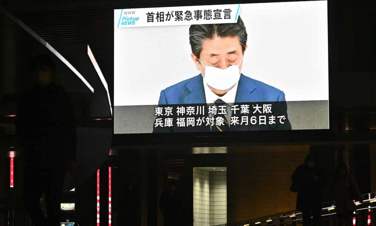 A screen shows news footage of Japan's prime minister, Shinzo Abe, declaring a month-long state of emergency.