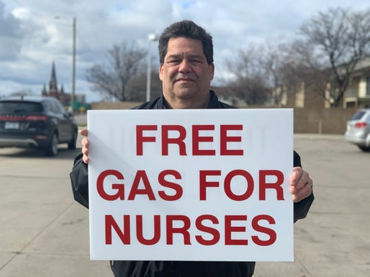 Allen Marshall, 60, of St. Clair Shores, holds a sign offering to buy free gas for nurses (Photo: Branden Hunter)