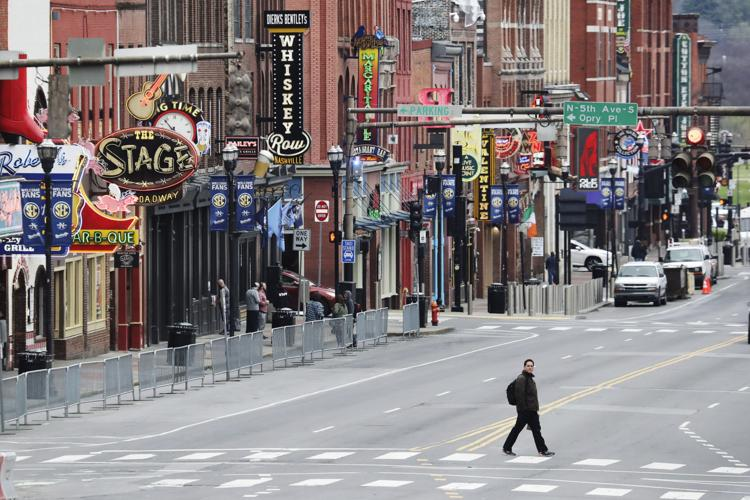 A man walks across Broadway, where the streets are usually filled and the sidewalks are usually crowded, on Monday, March 23, 2020, in Nashville, Tenn.