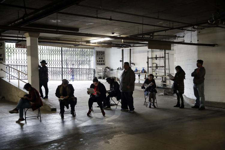 Unionized hospitality workers wait in line in a basement garage to apply for unemployment benefits at the Hospitality Training Academy Friday, March 13, 2020, in Los Angeles.