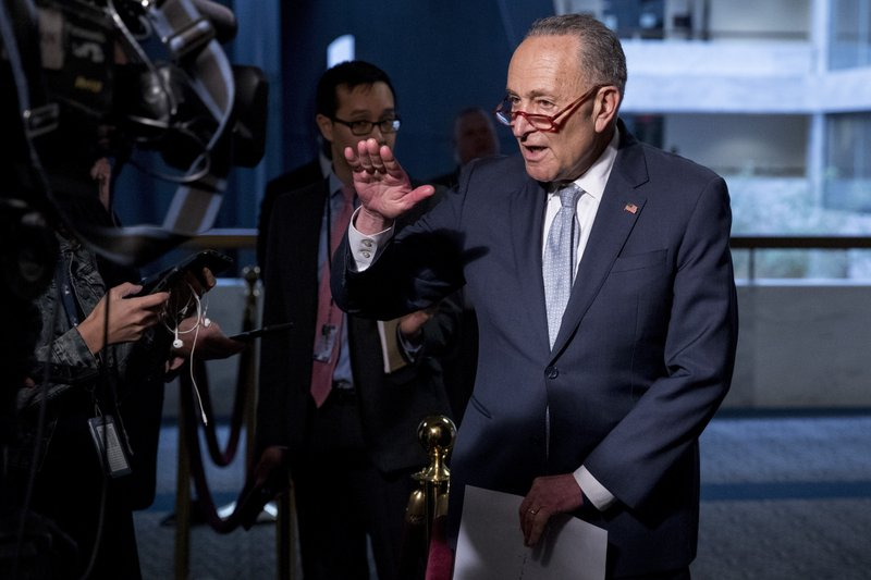 FILE - In this March 20, 2020, file photo Senate Minority Leader Sen. Chuck Schumer of N.Y., speaks to reporters as he arrives for a meeting to discuss the coronavirus relief bill on Capitol Hill Washington.