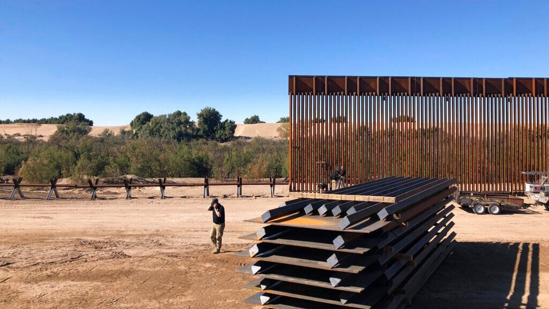 In this Jan. 10, 2020, photo, people work at a portion of border wall which is under construction in Yuma, Ariz.