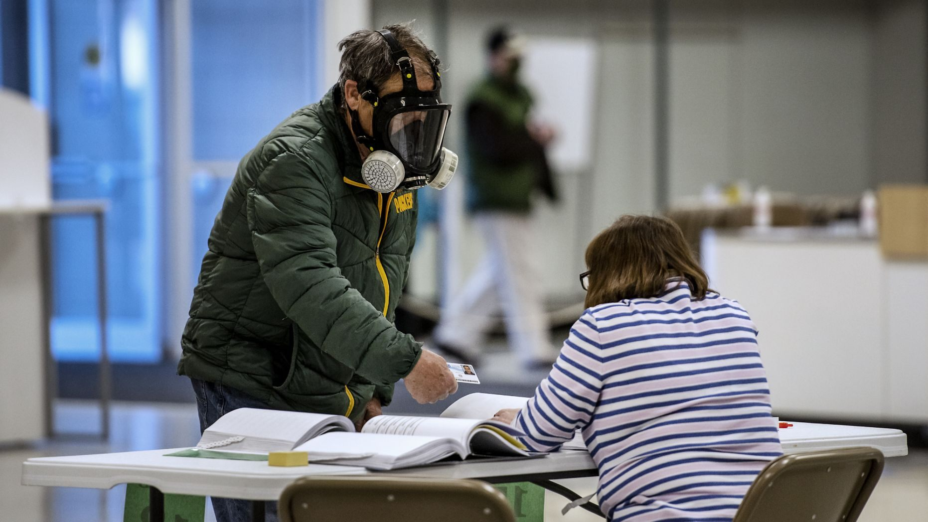 Robert Forrestal, left, wears a full face chemical shield to protect against the spread of coronavirus, as he votes Tuesday, April 7, 2020,