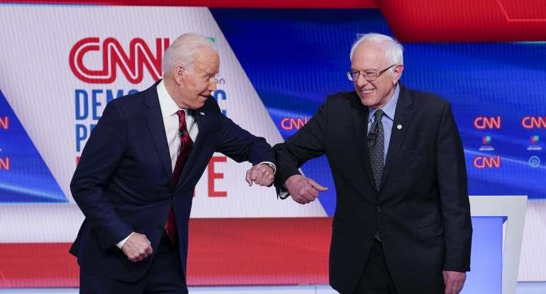 Former Vice President Joe Biden, left, and Sen. Bernie Sanders, I-Vt., right, greet one another before they participate in a Democratic presidential primary debate