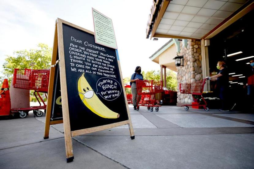A drawing of a banana wearing a face mask advises customers they must wear a covering over their mouth and nose before entering a Trader Joe's in Davis, Calif., Monday, April 27,