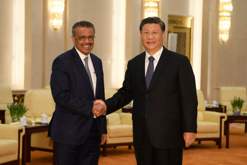 Tedros Adhanom Ghebreyesus (left), the director-general of the World Health Organization, shakes hands with Chinese President Xi Jinping