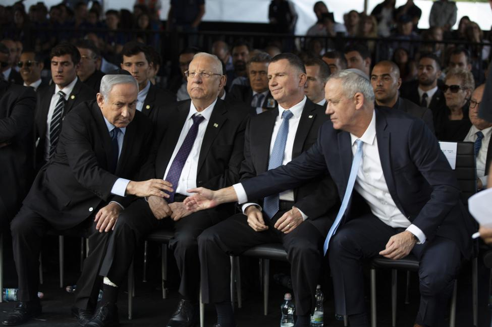 Blue and White party chief Benny Gantz (R) reaches out to shake hands with Israeli Prime Minister Benjamin Netanyahu