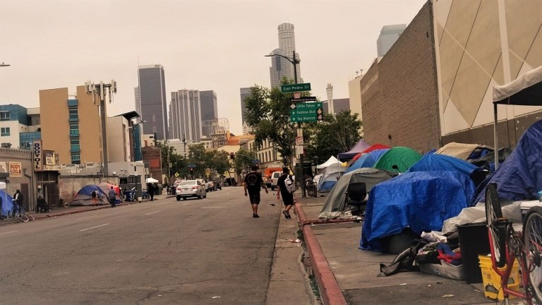 Tents, shelters and belongings line a street near downtown Los Angeles. (Nathan Solis / CNS)