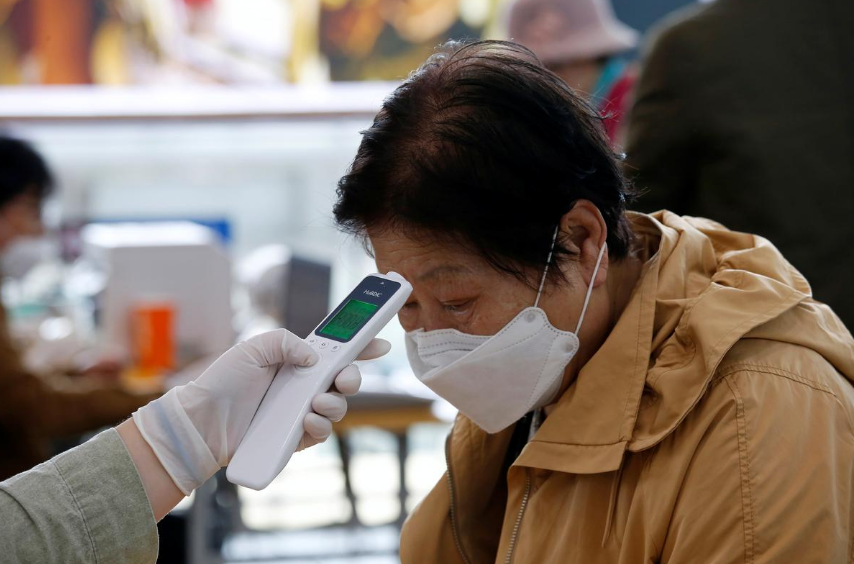 A woman wearing a preventive face mask has her temperature checked, as a safety measure to prevent the further spread of the coronavirus,