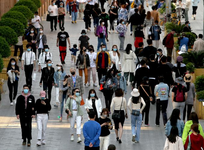 """Pedestrians no longer practice safe """"social distancing"""" but continue to wear protective face masks while visiting a popular entertainment area in Beijing on April 26."""