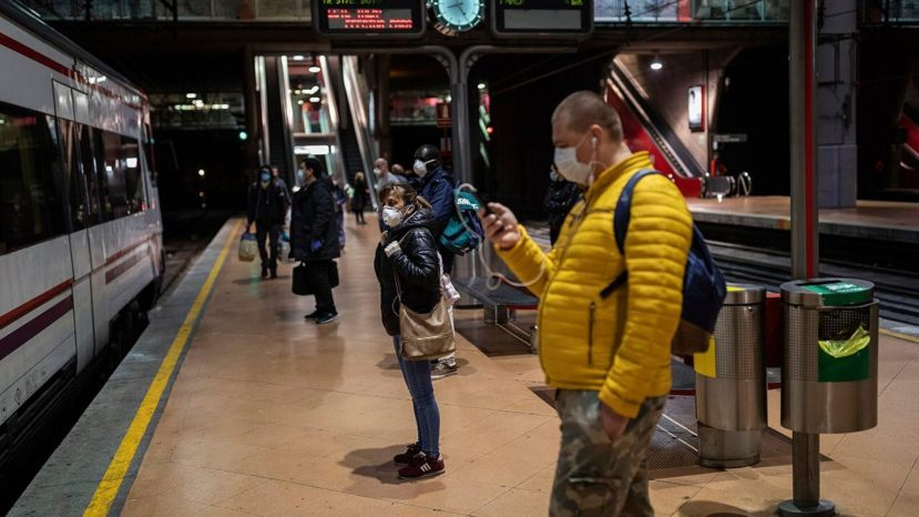 Commuters wearing face masks to protect against coronavirus wait at the platform of Atocha train station in Madrid on Monday.