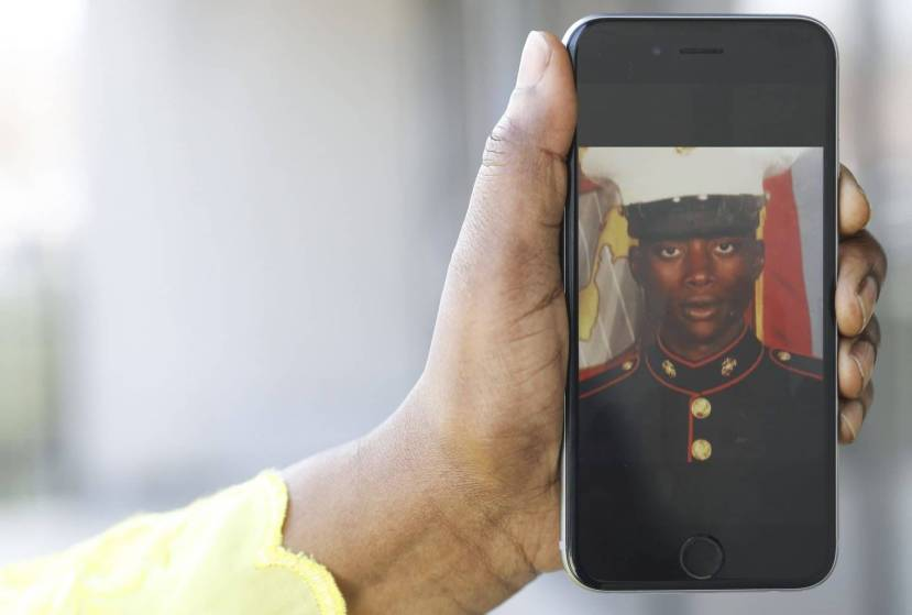 Fatoumata Balde, sister of Mamadou Balde, holds cell image of her brother as a Marine