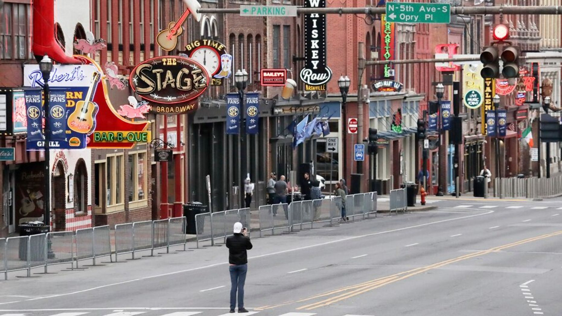 A man stands in the middle of Broadway to take a photo where the streets and sidewalks are normally filled in Nashville, Tenn. on March 23.