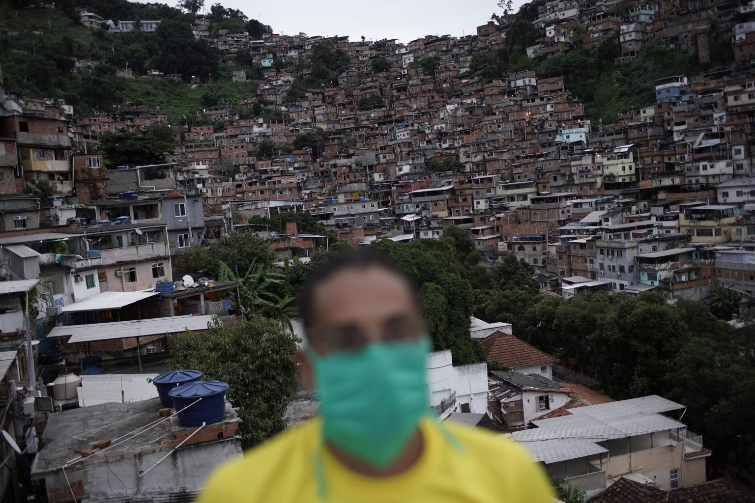 A worker protects himself against the coronavirus as he donates food to poor families in Turano favela,