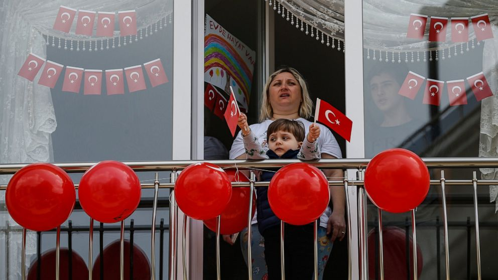 Local residents, in their flat due to the coronavirus, watch celebrations ahead of the National Sovereignty and Children's Day, in Istanbul, Wednesday, April 22, 2020.