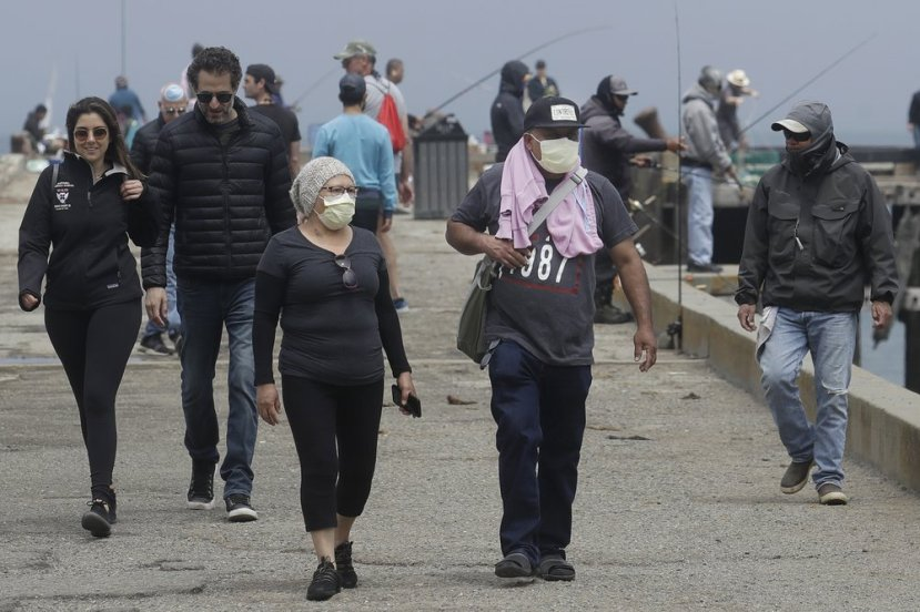 Some people wear face masks while walking on a pier during the coronavirus outbreak in San Francisco, Saturday, May 16, 2020.