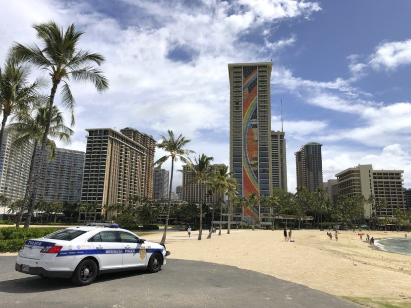 FILE - In this March 28, 2020, file photo, a police officer arrives to tell people to leave Waikiki Beach in Honolulu.