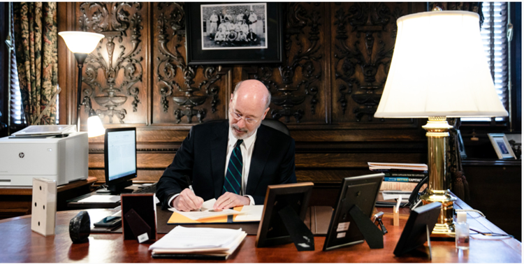 Pennsylvania Gov. Tom Wolf signing a disaster declaration for COVID-19 at his desk on March 6, 2020.