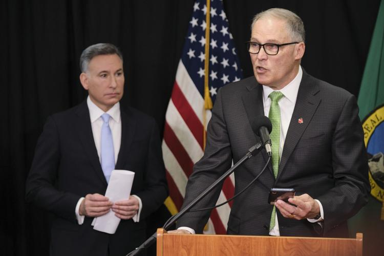 Washington Gov. Jay Inslee reads from an email from his mobile phone as he talks to reporters while King County Executive Dow Constantine listens,