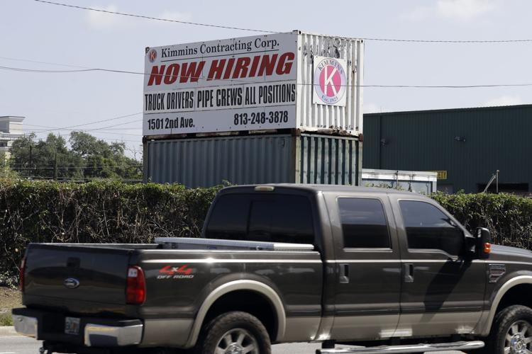 Drivers pass a sign outside the Kimmins Contracting Corp. on Thursday, March 26, 2020, in Tampa, Fla.