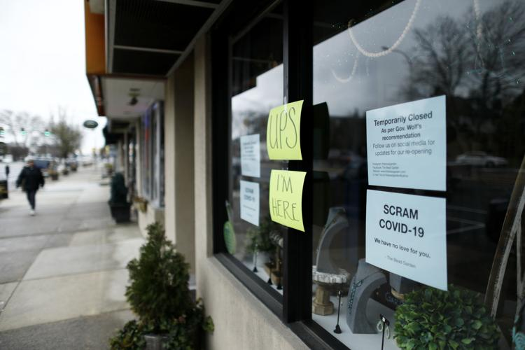 A person walks past a closed craft store March 17, 2020, in Havertown, Pa. Concerns about the new coronavirus have led to the temporary closure of many businesses and schools across the region.