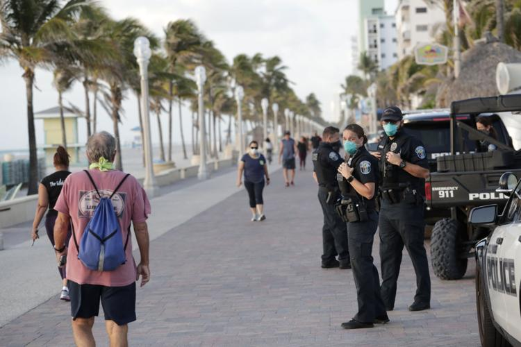 Hollywood, Fla., police officers monitor activity along the Hollywood Beach Boardwalk on Wednesday, May 13, 2020.