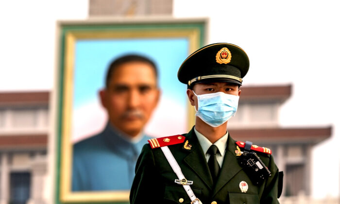 A Chinese police wearing protective masks march in front of the portrait of Nationalist founder Sun Yat-sen at Tiananmen Square in Beijing,