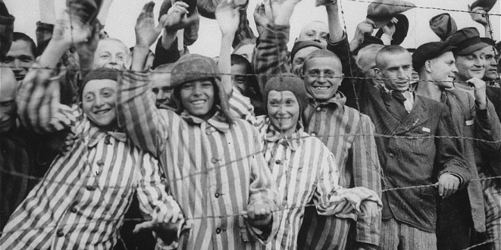 Survivors at the Dachau concentration camp cheer their liberation by US soldiers.