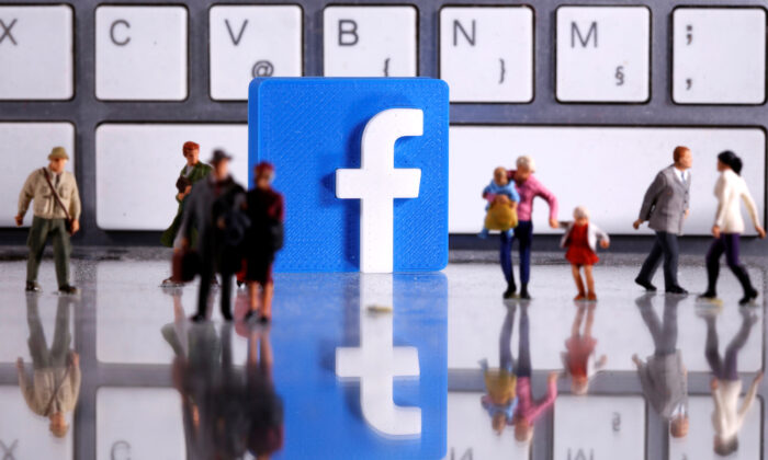 A 3D printed Facebook logo and toy people figures in front of a keyboard in this illustration taken on April 12, 2020.