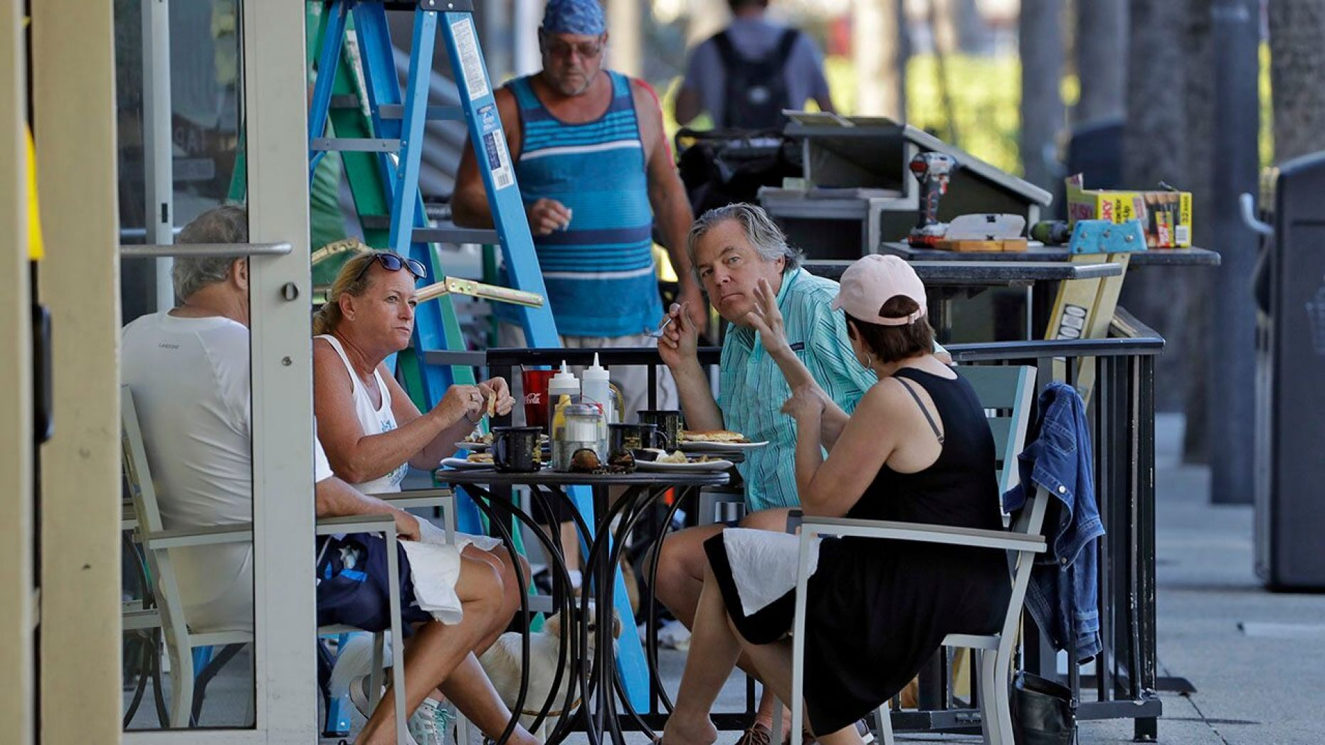 People have breakfast at a cafe Monday in Clearwater Beach, Fla.,