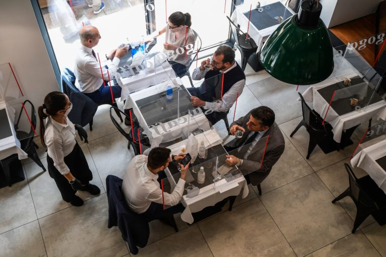 A general view shows people having lunch at tables partitioned with plexiglas at the Goga Cafe on May 18, 2020 in central Milan.