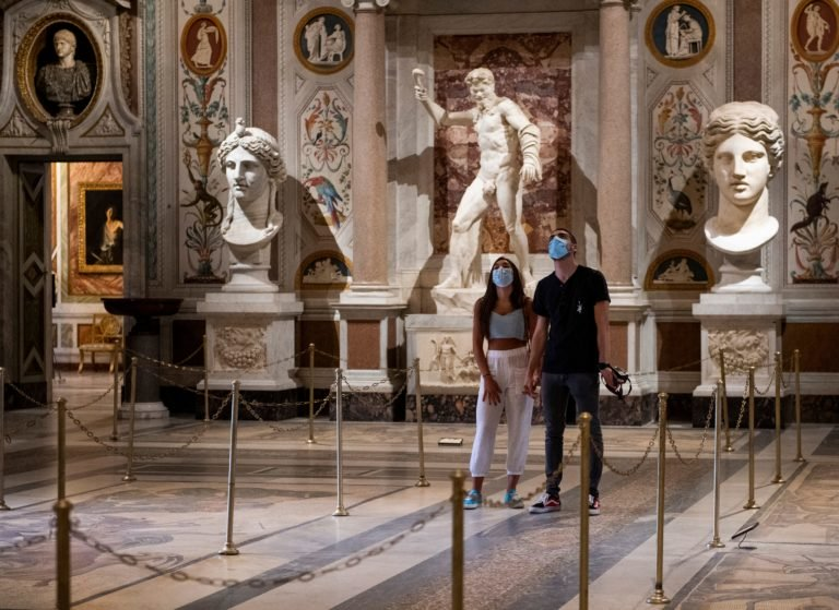 Visitors wearing a face mask view a room at the Galleria Borghese museum in Rome on May 19, 2020,